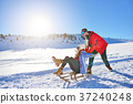 Young Couple Sledding And Enjoying On Sunny Winter 37240248