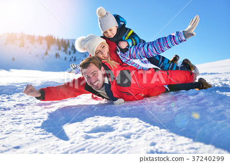 happy young family playing in fresh snow at 37240299