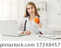Smiling nutritionist woman with orange at office 37248457