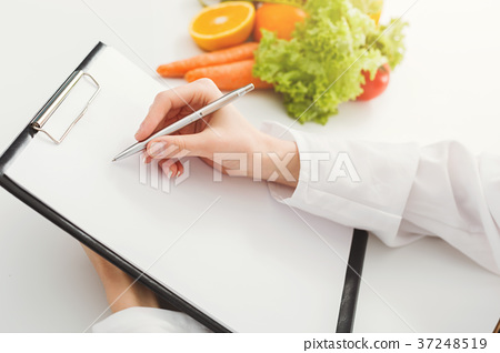 Nutritionist doctor writing diet plan on table 37248519