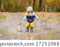 Happy child jumping on puddles in rubber boots 37252068
