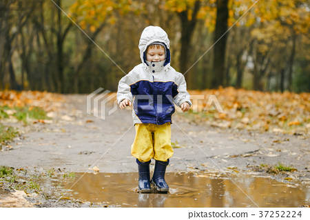 Happy child jumping on puddles in rubber boots 37252224