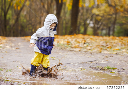 Happy child jumping on puddles in rubber boots 37252225