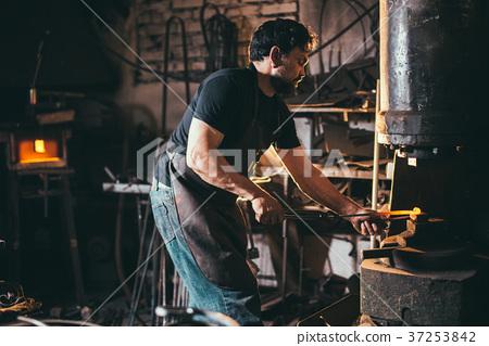 male blacksmith shaping metal in hammer machine 37253842