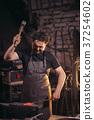 Senior blacksmith forging molten metal on the 37254602
