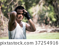 A Boxer practices his boxing step in a park. 37254916