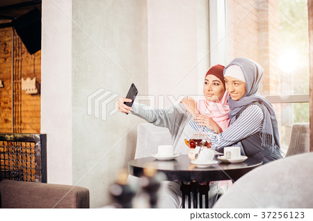 excited young muslim girl friends taking selfie 37256123