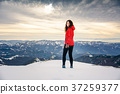 Female hiker on snow covered mountain top 37259377