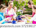Family having coffee time in garden eating cake 37259617