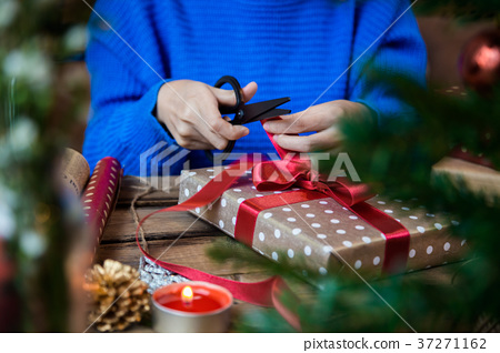 Cutting red ribbon for wrapping present 37271162