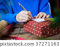 Writing message in a card and giving present 37271163