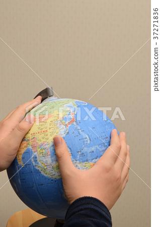 Child's hand wrapping world globe 37271836