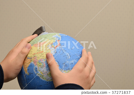 Child's hand wrapping world globe 37271837