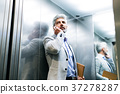 Mature businessman with smartphone in the elevator 37278287