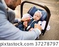 Father with baby daughter sitting in car safety 37278797