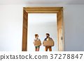 Young couple moving in new house, holding boxes. 37278847