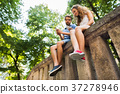 Young couple with smartphones in town sitting on 37278946