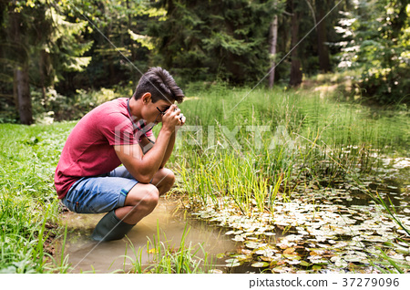 Teenage boy with camera in the lake, taking 37279096