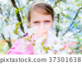 Allergy. Little girl is blowing her nose near tree 37301638