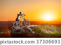 Cyclist with mountain bike on the hill in the evening 37306693