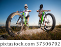 Cyclists with mountain bikes on the hill under blue sky 37306792