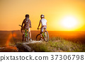 Cyclists with mountain bikes on the hill in the evening 37306798
