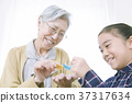 Grandma and girl folding origami 37317634