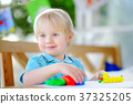 Creative boy playing with colorful modeling clay at kindergarten 37325205