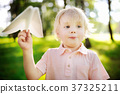 boy playing with paper plane in a summer park 37325211