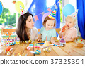 child and their mother celebrate birthday party 37325394