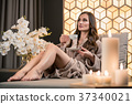 Relaxed young woman drinking herbal tea before spa 37340021