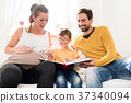 Parents showing their firstborn son pictures in 37340094