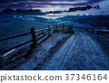 fence along the country road at night 37346164