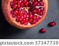 Sliced pomegranate with juicy red grains 37347739