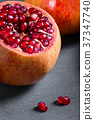 Sliced pomegranate with juicy red grains 37347740
