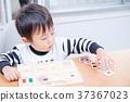 เด็กวัยหัดเดินเล่นกับปริศนาธงชาติที่โต๊ะอาหาร 37367023