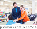 Couple in baby shop buying stroller 37372516