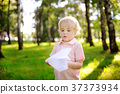 Cute toddler boy playing with paper plane in a summer park 37373934