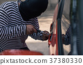 Car thief trying to unlock a car by screwdriver 37380330