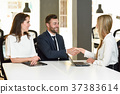 Smiling young couple shaking hands with an insurance agent 37383614
