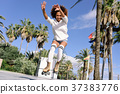 Black woman, afro hairstyle, on roller skates jumping near the b 37383776