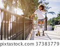 Black woman, afro hairstyle, on roller skates riding near the be 37383779