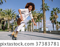 Black woman on roller skates rollerblading in beach promenade wi 37383781