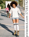 Black woman on roller skates rollerblading in beach promenade wi 37383782