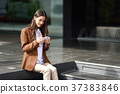 Businesswoman texting with a smartphone next to an office buildi 37383846