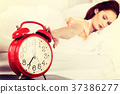 Sleeping woman with her hand touching alarm clock 37386277