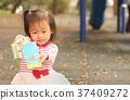 一位亚洲女孩在公园看书阅读 37409272