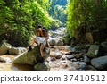 Asian Women hiker with backpack checks map  37410512