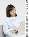 演奏在长沙发的少妇计算机 37412219