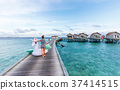 Asian woman holding pegasus pool float at Maldives. 37414515
